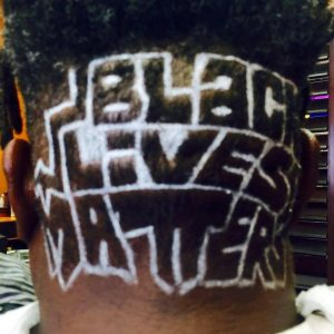 "The back of a head with ""BLACK LIVES MATTER"" visible on it."