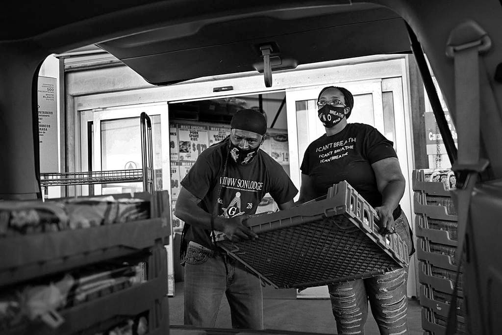 A black-and-white photo. Two adults in masks load a palette into the back of a truck.