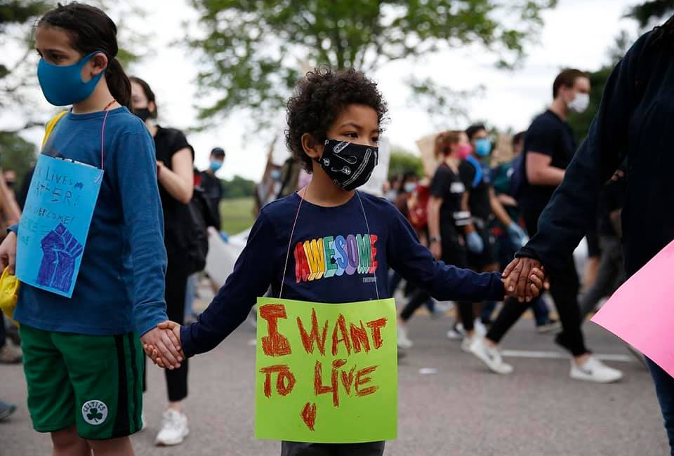 "A masked child marches in a protest. They carry a sign reading ""I WANT TO LIVE."""